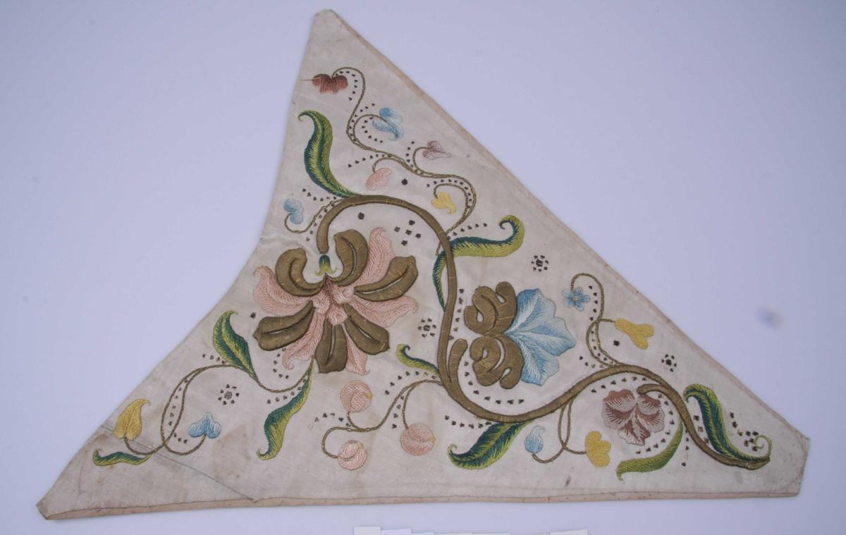 Nesten likesidet trekant, avrundet i halsen, av hvit moirè. Den har broderi i rosa, grønt, rødbrunt og gult i flere sjatteringer i silke og dessuten broderi av gulltråd over opphøyd underlag av papp. Mønstret er en bølget gullranke med utskytende blomster og blad i gulltråd og silke. Små biter av metallbånd som paljetter innimellom. Fôr av hvit lin som stikker frem på sidene.