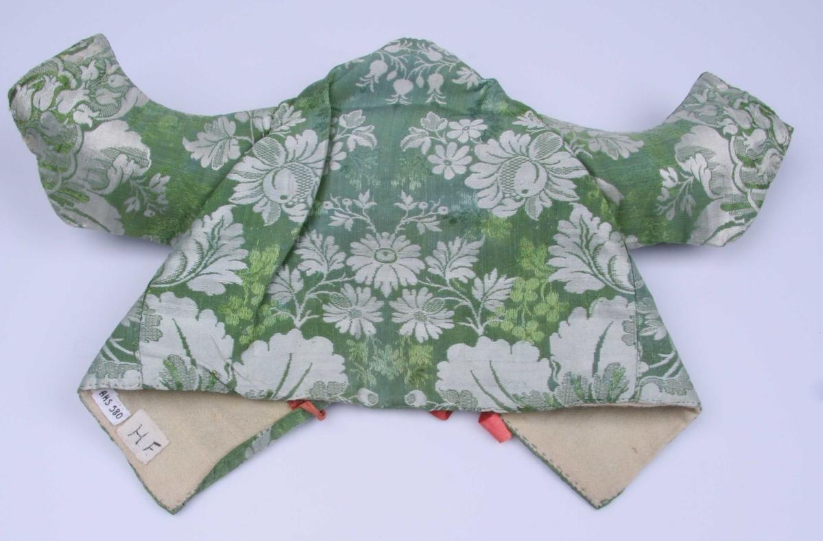 Av brokade i grønt og sølv, blomstret og med grønne brocherte blomster. Underarm-sømmen er plassert nesten oppe ved skulderen. Ermet har splitt nederst og spor etetr påsydd rødt silkebånd. Røde silkebånd til å knyte bak. Hvitt vadmelsfôr.
