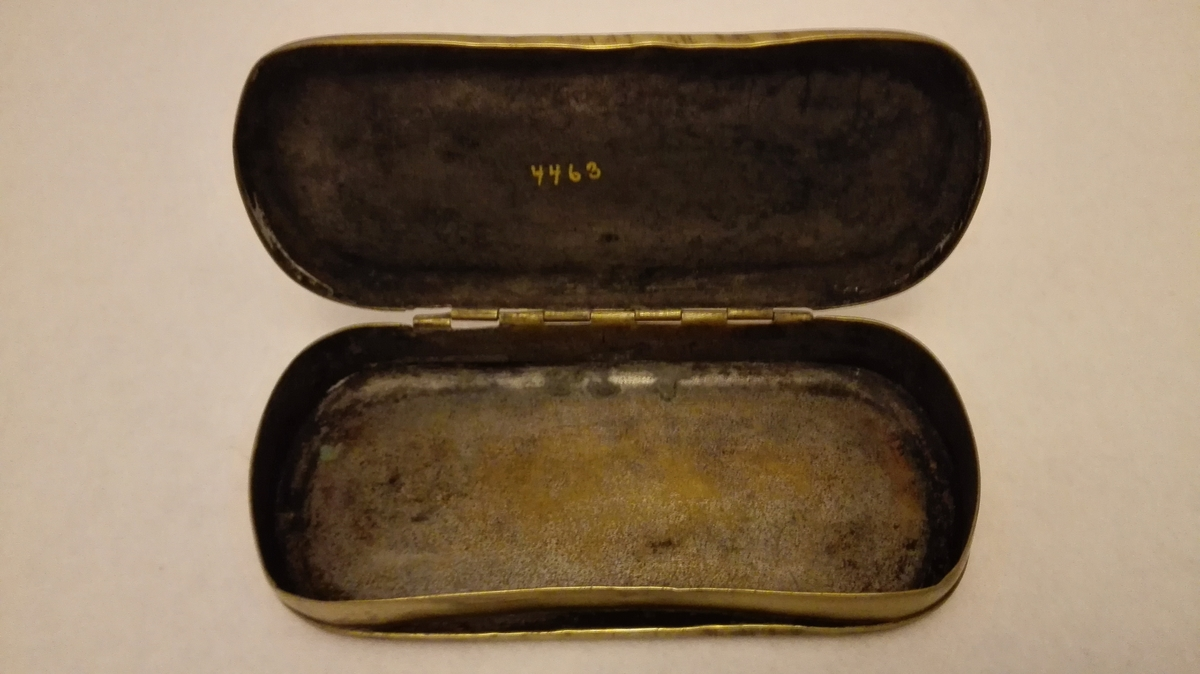 1 tobaksdaase av messing.    En saakaldt almanakdaase av svensk fabrikat. Fra O.W.Hedenstrøm 1827. Oval, firkantet med avrundete hjørner. 12,7 cm lang og 6 cm bred. Gave fra Mikkel S. Mundal, Fjærland.