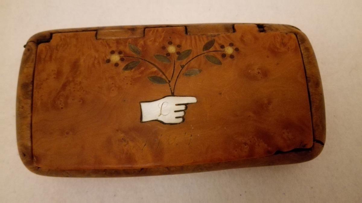 Form: Rektangulær dåse med lok. Avrunda hjørner. Innrissa årstal på loket samt framstilling av ei hand med blomar i perlemor og ulikt farga horn.