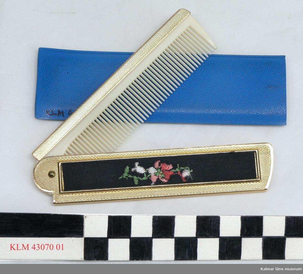 KLM 43070:1 Kam, plast, metall. Långsmal kam av vit plast, hopfäst i ena kortänden med en handtagsdel av gul metall med litet broderi. Kam och handtag kan vikas ihop. Med rektangulärt fodral av klarblå plast.
