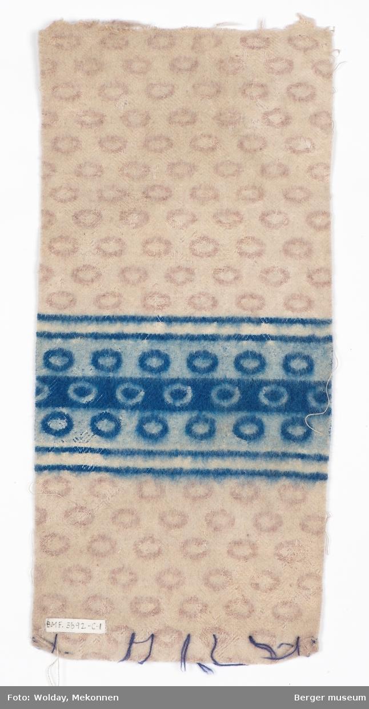 En prøve. Teppe med ovaler som blir brutt av samme mønsterbord i blått. Borden er adskilt av en hvit stripe med en smal brun stripe på hver side.