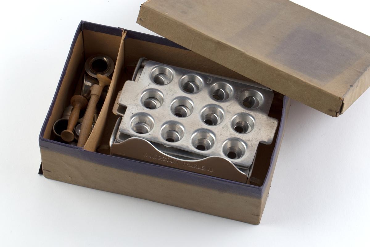Morstadts kapselapparat i original pappeske. Det samme apparat kan brukes til å lage kapsler av forskjellige størrelser. Apparatet er av aluminium, jernblikk/forniklet og består av fire plater. 2 plater er festet sammen med hengsler og 2 er løse. Esken inneholder også 3 trakter og 5 begere  i metall, og 3  stoppere av tre.