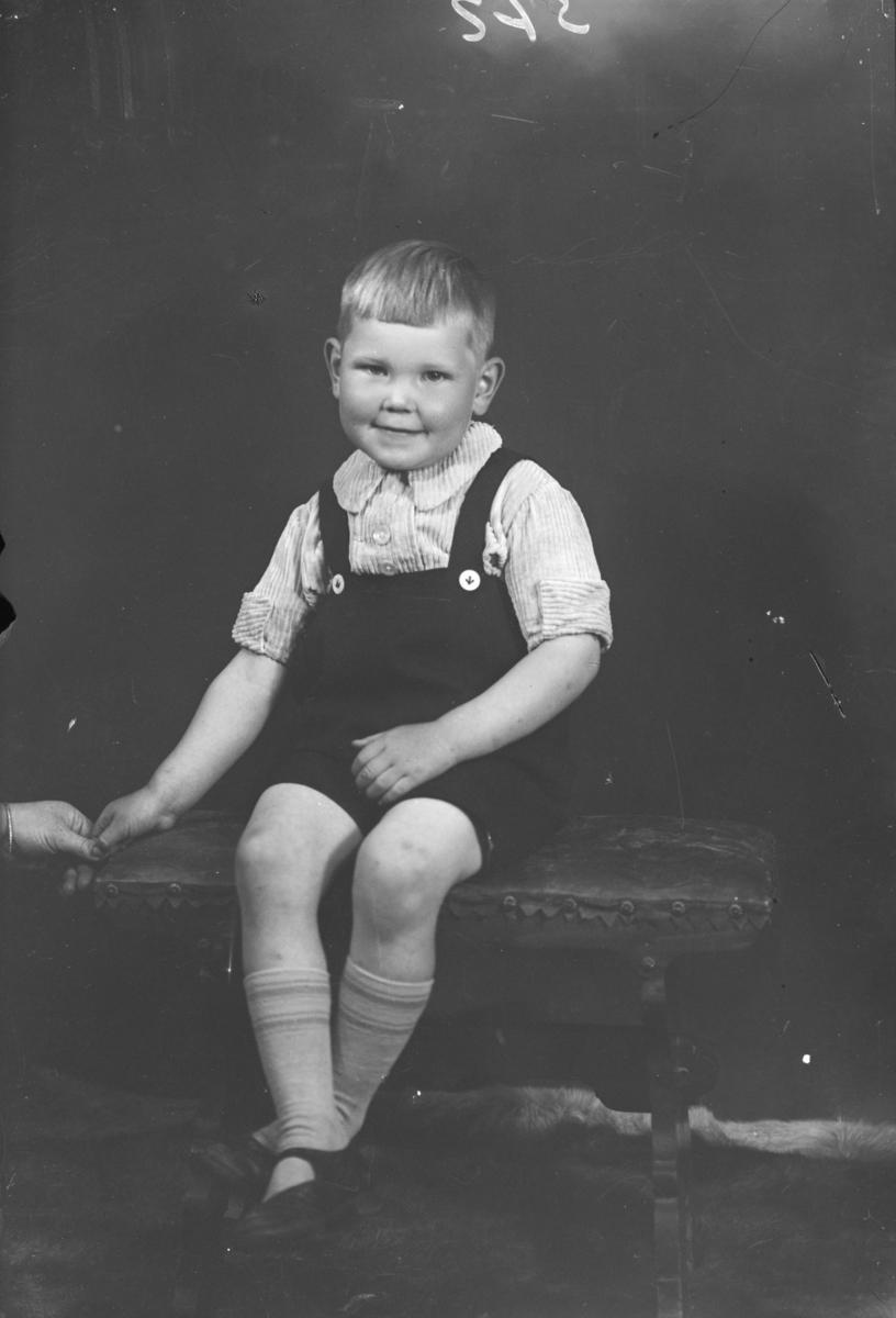 Gutt sitter på krakk. Helfigur. Antatt mor Ragnhild Eistre.