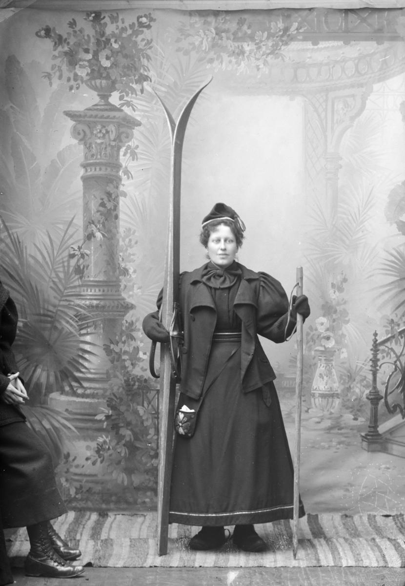 """Portrett, ung kvinne i """"skiantrekk"""" med ski og staver, Frøken Bjelke"""