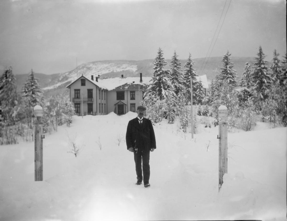 Stort hus med mann i forgrunnen, vinter
