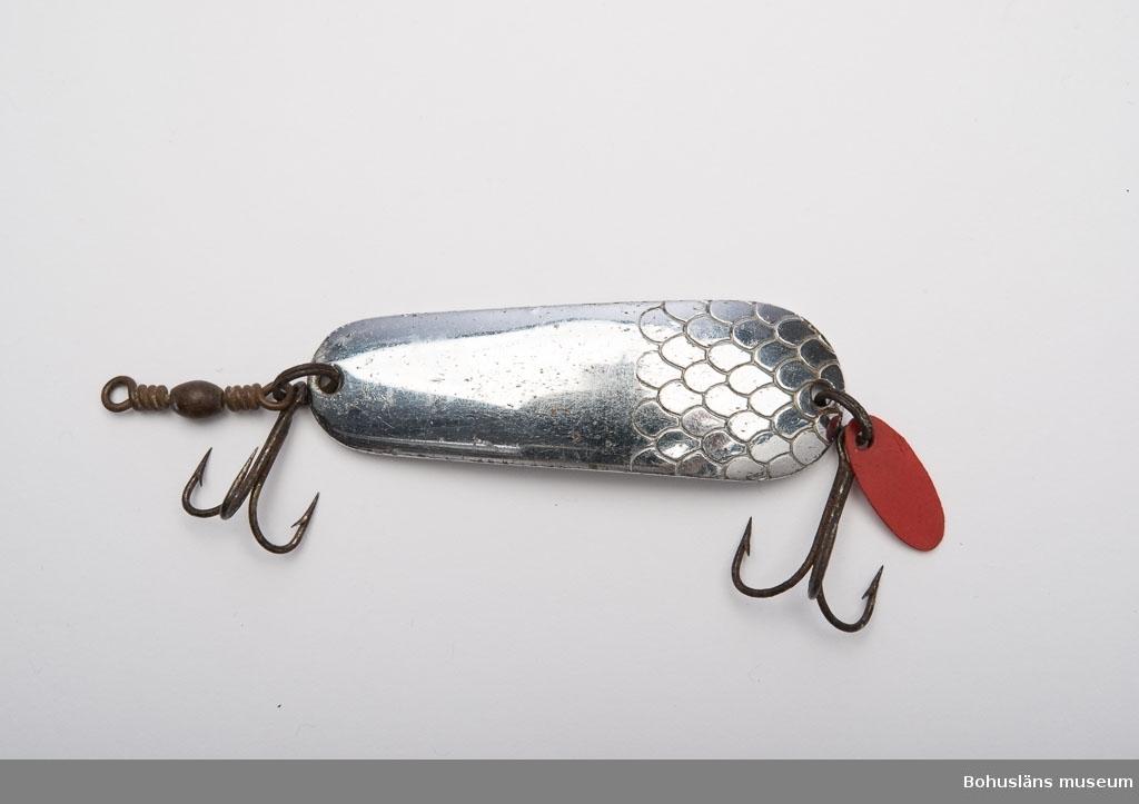 """Avlångt. Rundande kanter. Lätt buktat. Kromat. På ena sidan (baksidan) finns en fisk samt bokstäverna """"HJA"""" instansat. På framsidan är det instansat imitation av fiskfjäll. En trekrok i varje kortända. Vid den ena kroken är det en röd oval av konstmaterial. Vid den andra kroken är det en lekare (en roterande metallögla). Tillhör fiskeutrustning UM024251."""