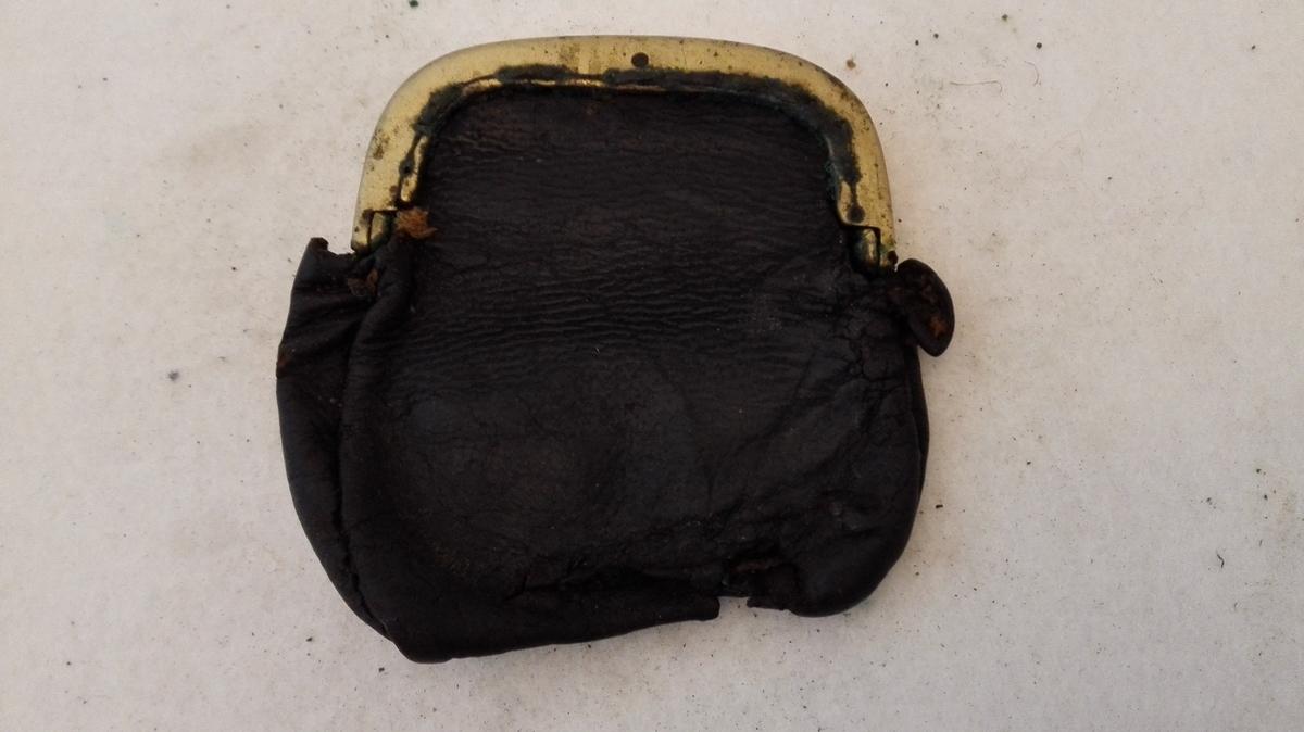 Pung av skinn, med lås av messing. Låsen vert opna ved å trykka ned eine sida av toppen på pungen. Pungen har to rom, men er mykje defekt.