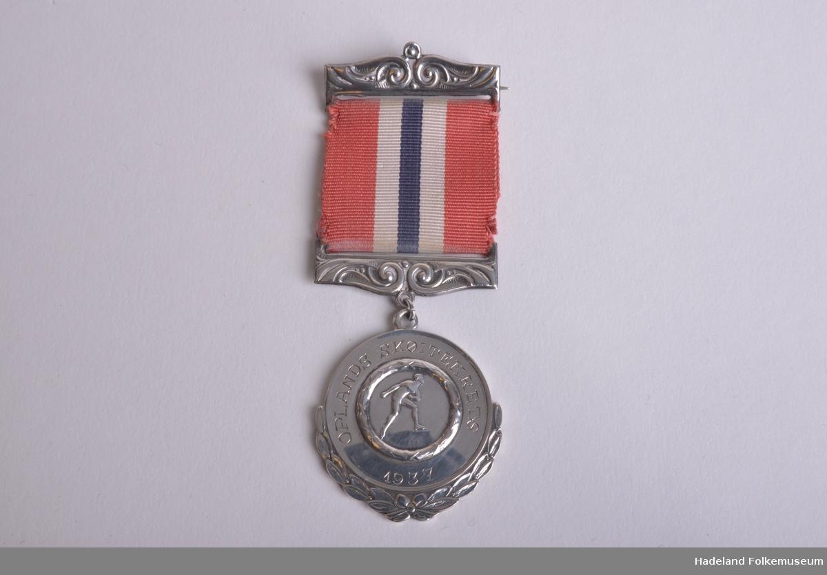 """Sølvmedalje, stemplet 830s Lo. Krans rundt nedre halvdel. Krans rundt skøyteløperfigur i midten. Utenpå står det """"Opland Skøytekrets 1946"""" Henger i nasjonalfarget bånd med to beslag."""