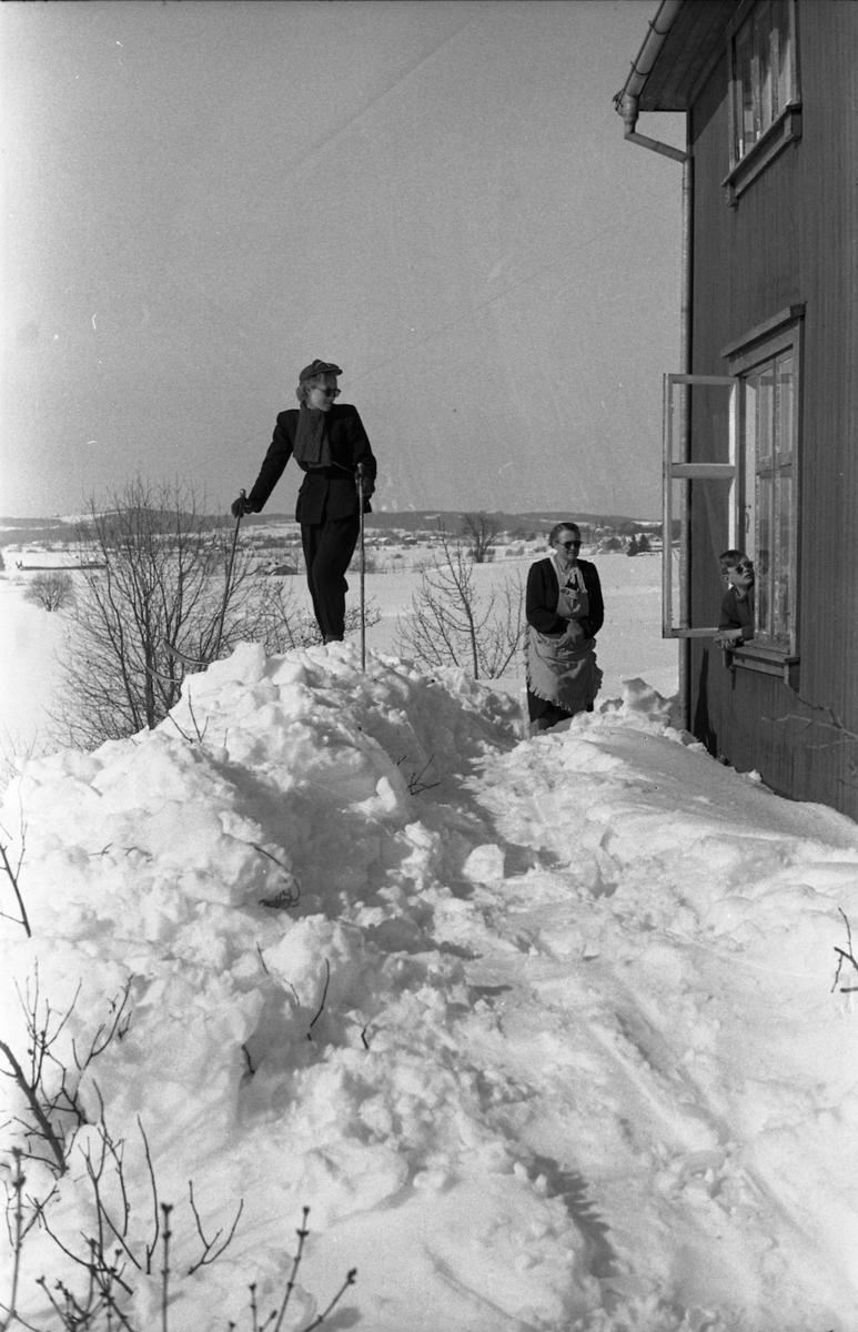 To bilder fra fotografens eiendom Odberg på Kraby mars/april 1951. På bilde nr. 1 Sigrun Røisli på ski, bror Kjell som sitter på sparken med forstuet ankel, og mor Karine som med nød og neppe finner postkassa inne i snøhaugen. På bilde nr. 2 Sigrun Røisli og mor Karine på baksida av huset, mens Kjell kikker ut av vinduet.