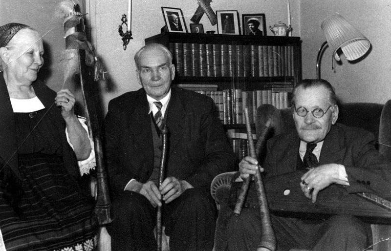 """Från vänster: karelskan Elmi Tshokkinen, en av Finlands sista gråterskor och runosångerskor, spinnande på en """"Värttina"""", Olov Olovsson från Velen och Finlands mest kände folkspeleman Peppo Repu, till börden ingermanländare med egenhändigt förfärdigade kantele och näverflöjter."""