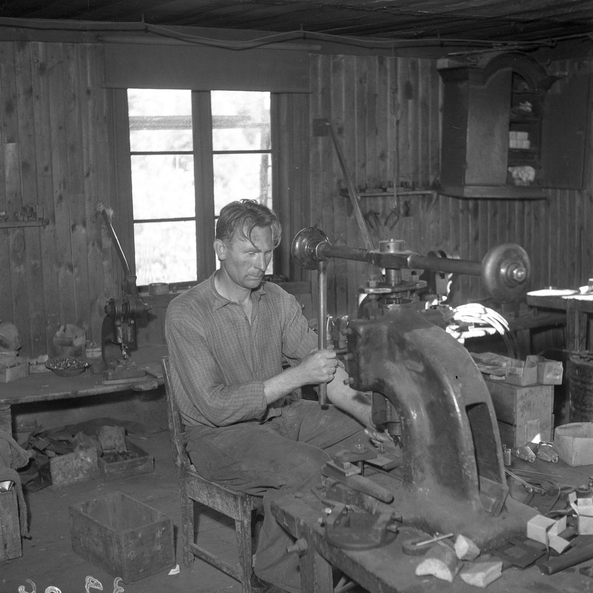 Erik Johansson stansar hål med maskin. Kläppen svetsas samman med gas, en tunnare och en tjockare klamp.