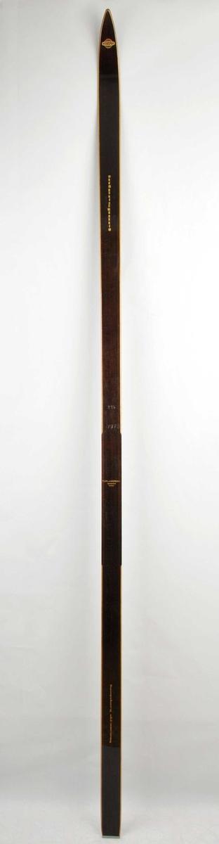 Langrennski laga av tre. Brunlakkera overflate, trekvite sidekantar. Intersport-emblem i framtupp. Metallbeslag på baktupp.