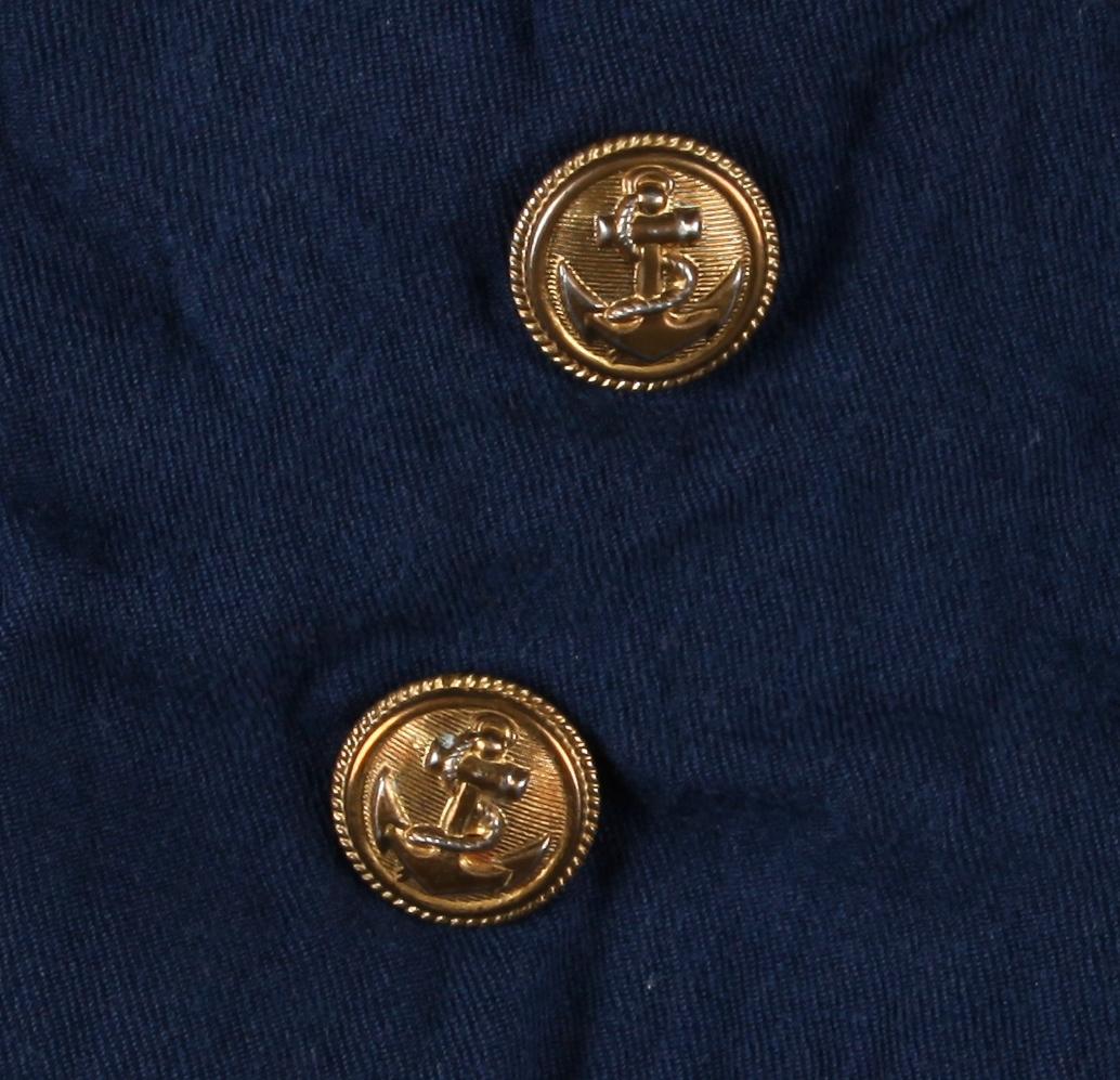 Mørk blå bluse med splitt midt framme, isydde armar, legg mot linning på armane, stor krage med kvitt pynteband, lita passepoilert lomme på v side, linning i livet (i eit anna slag stoff), glidelås i h side. Fôra i bolen. To knappar med ankermotiv sydd under lomme (to knappar på v side truleg fjerna, - rest etter tråd på baksida). Svart merke med norsk flagg sydd på v arm; raudfargen i flagget er borte (slitasje eller fjerna?) Storleik ca 2 - 3 år. Tydeleg omsaum, heimesydd