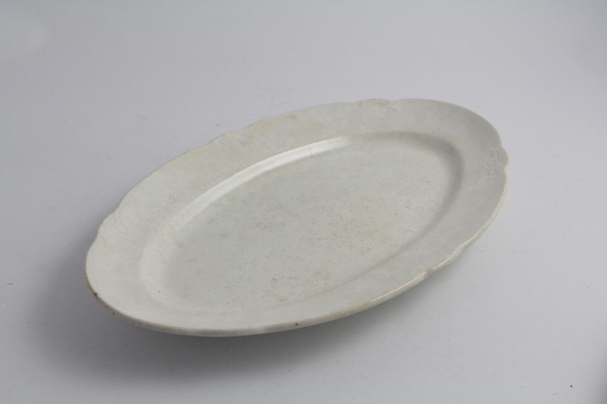 Serveringsfat, ovalt, avlangt i hvitt. Ikke stemplet. Relieff i form av små blomsterkvister på fane.