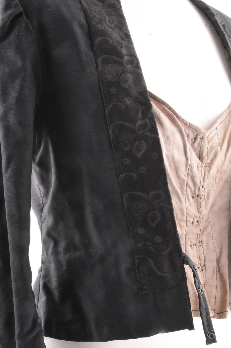 Trøye av svart ullsateng med besetningar av svart mønstra silke rundt nakken og ned framme, samt nederst på armane. Open midt framme der det er sydd fast tre hekte på kvar side, truleg for feste av bringeklut (denne manglar).  Nedest på ryggstykket er det isett tre kilar, i den mideste av desse er det sydd fast eit hekte (til feste av stakk?). Rett isydd tosaumsarm, der overarmdelen er lengre enn underarmdelen. Overarmen går ned i spiss ved handleddet. Trøya har fòr og innerliv av beige kypertvove bomullstøy. Innerlivet er rundringa og festast saman med seks hekter midt framme.