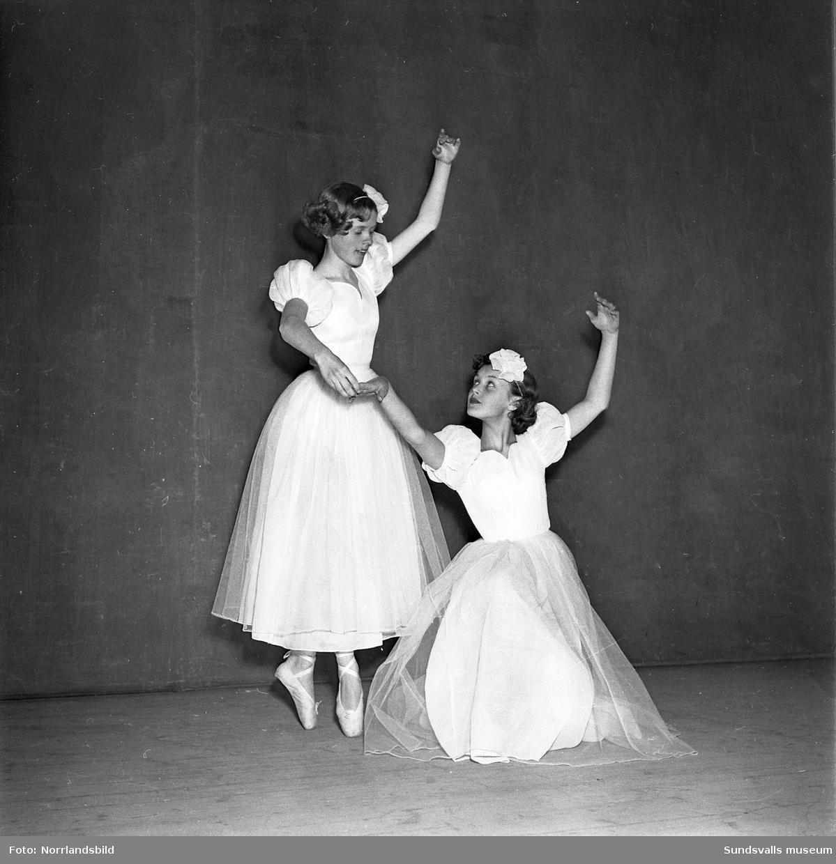 Två ballerinor poserar på en scen.