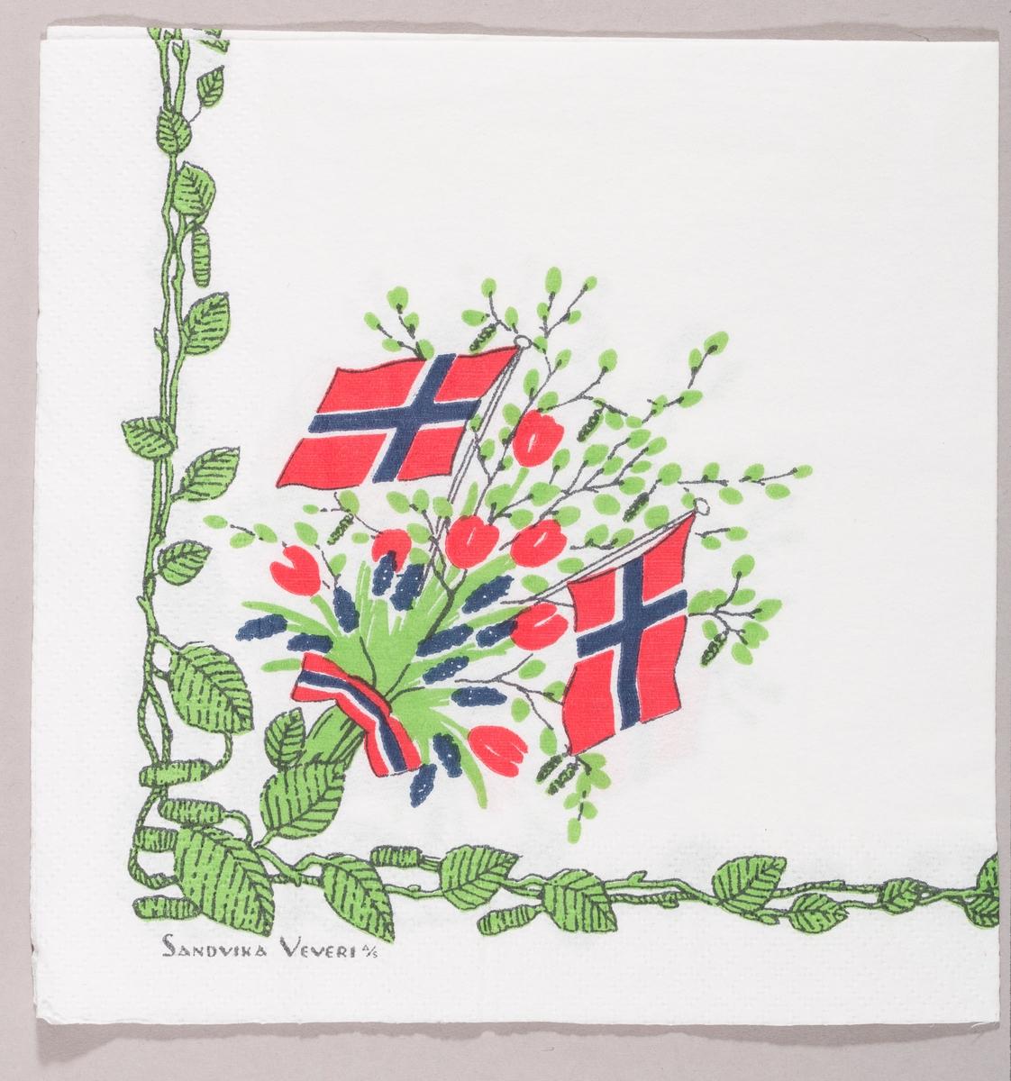 To norske flagg i en bukett med grønne bjørkegrener og røde og blå blomster. En bord med grønne blader og rakler.