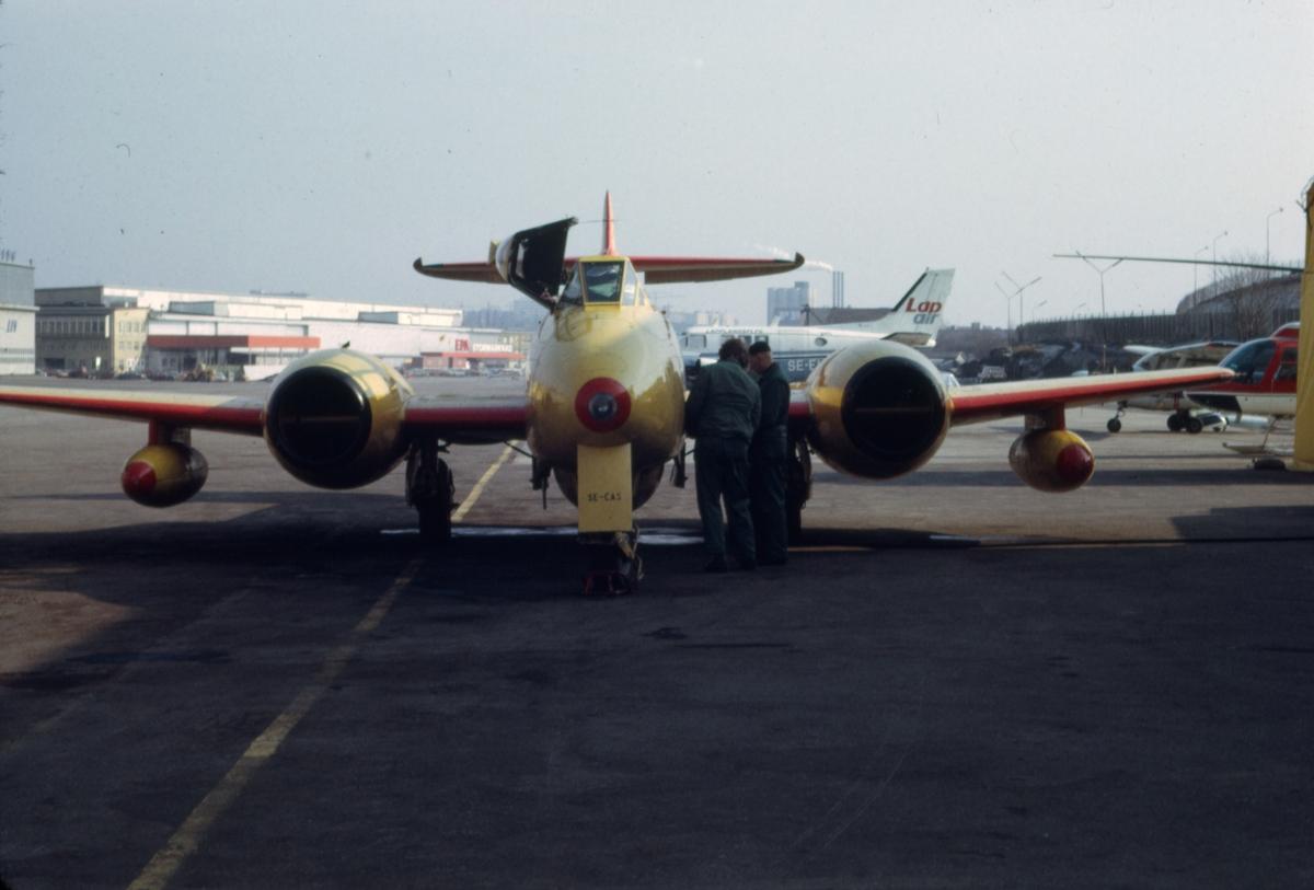 Gulmålat målbogserflygplan av typ Gloster Meteor T.7 med civilt registreringsnummer SE-CAS på Bromma flygplats, i början av 1970-talet. Flygförare och flygtekniker i arbete. Serie om 7 bilder.