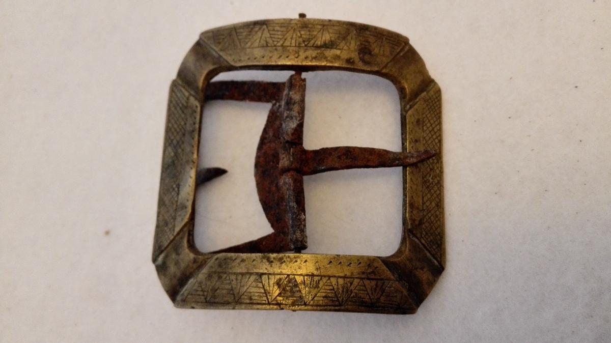 Form: Firekanta  2 par messing skospænder.  No 4673 firkantet med brudte hjørner paa forsiden forsirt med strekornamenter. No 4674 oval firkantet forsirt med støpte ornamenter. Gave fra Jens A. Aafet, Feios.