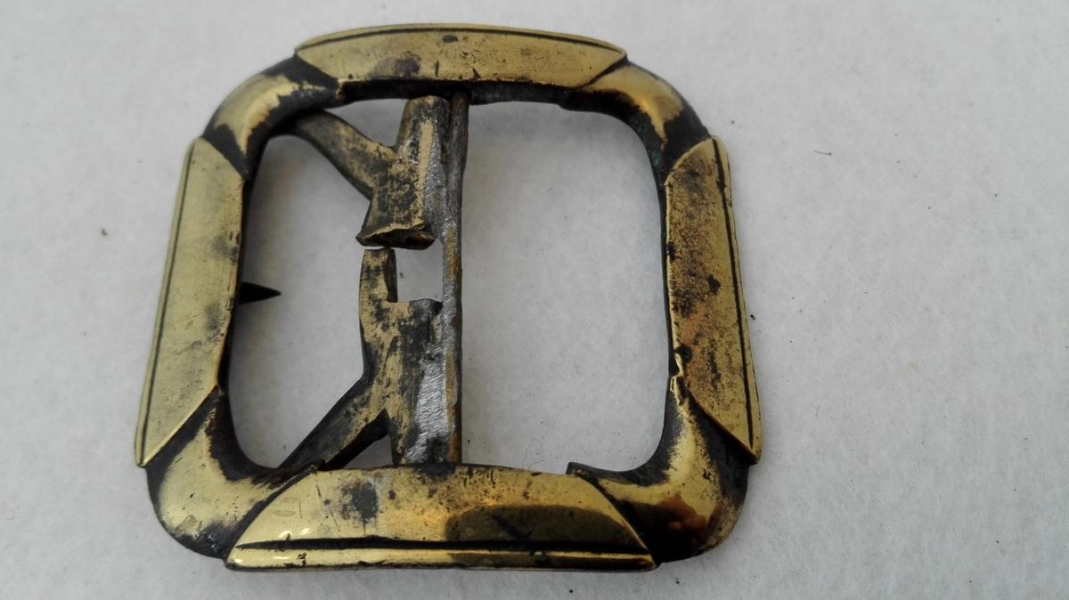 Form: Firkanta med avrunda hjørner. 3 messing skospænder (10120 - 22).  Tre messing skospænder alle av forskjelig störrelse.  10122 - Samme type som foregaaende, tand mangler 5,4 x 5,2 cm.  Kjöpt av Kristoffer Kvale, Sogndal.