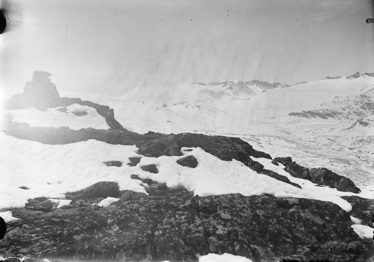 Fjellandskap fra fjelltopp med varde, vinter. Antatt fra Jotunheimen