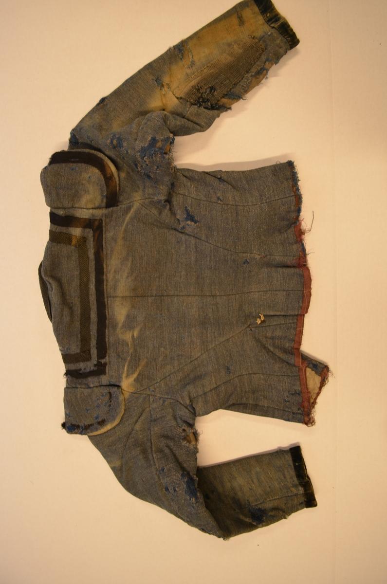 Kjoleliv for jente i blått kypertvove ulltøy, fóra med med tynt ulltøy. Opning framme med 8 hekter og 8 krokar på innsida, smal halslinning. Ermane er kanta nederst med svart fløyel.