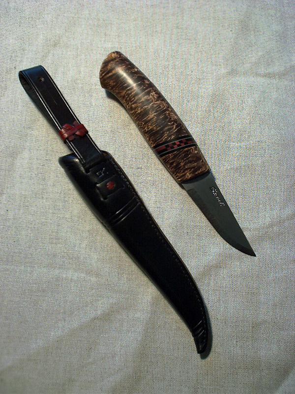 Emballasje: Papprøyr m/plastlok og silkepapir. Innfelt lita stripe med raud/svart sjakkmønster. Pauta slire