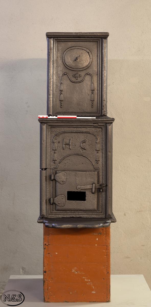 Etasjeovn. Firkantet ovn i to etasjer med ovnsdør og askebrett på kortside. På langsidene 1. etg Kroningsregaliene på barokk sokkel med løvverk på sidene og i midten den norske løve i skjold. Innrammet med en springlist. 2. etg har rette hjørner med en halvrund åpning på langside platene.