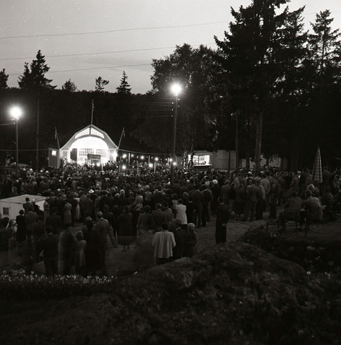 """Kvällsfest på """"berget"""" i Söderhamn augusti 1953. En man står framför en mikrofon på en upplyst utescen med skylten SGU. Framför sitter en stor publik."""