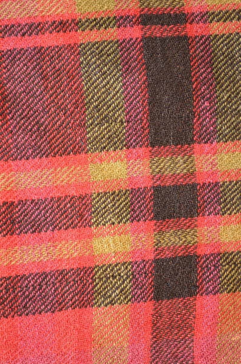 Sjal, ruta ullsjal i raudrosa, svart, fiolett og grønt ullgarn. Kypertvoe. Samansydd av to høgder. Falda for hand langs sidene.