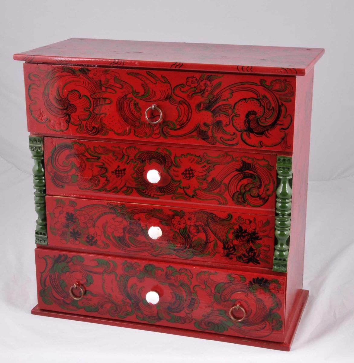 Liten komode, dreia søyler i kvar side av front, fire skuffar med porselensknott eller ring som handtak. Raud botnfarge med dekor i svart og grønt.