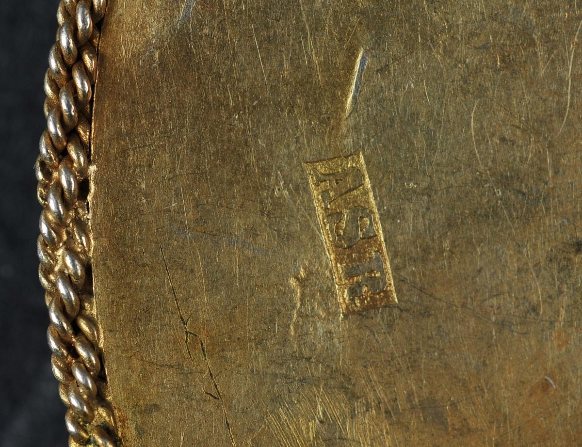 Heil botn. Ein ring langs ytterkant med krusar som vekslar mellom kule og diamant på toppen. Innanfor ligg eit felt med rosur som er nagla fast i boten, denne er ikkje gylt. På dette feltet er det nagla fast seks innfatta raude steinar. Fast torn. Sekundær nål. Stempla av produsent.