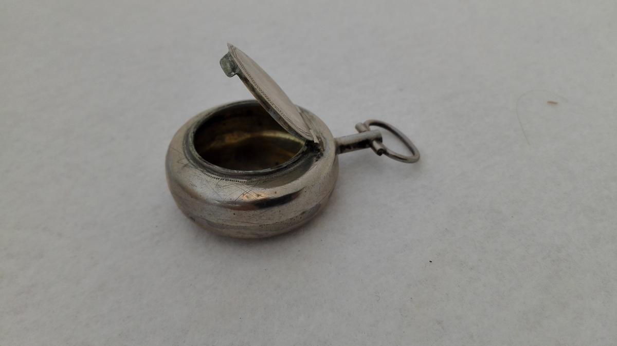 Form: Klokkeforma, med lok på den eine sida.