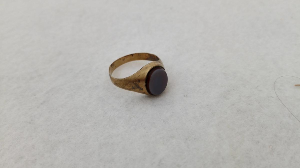 Form: Ringforma med høga innfatning for stein. Utvida ved innfatninga. Innfelt stein.
