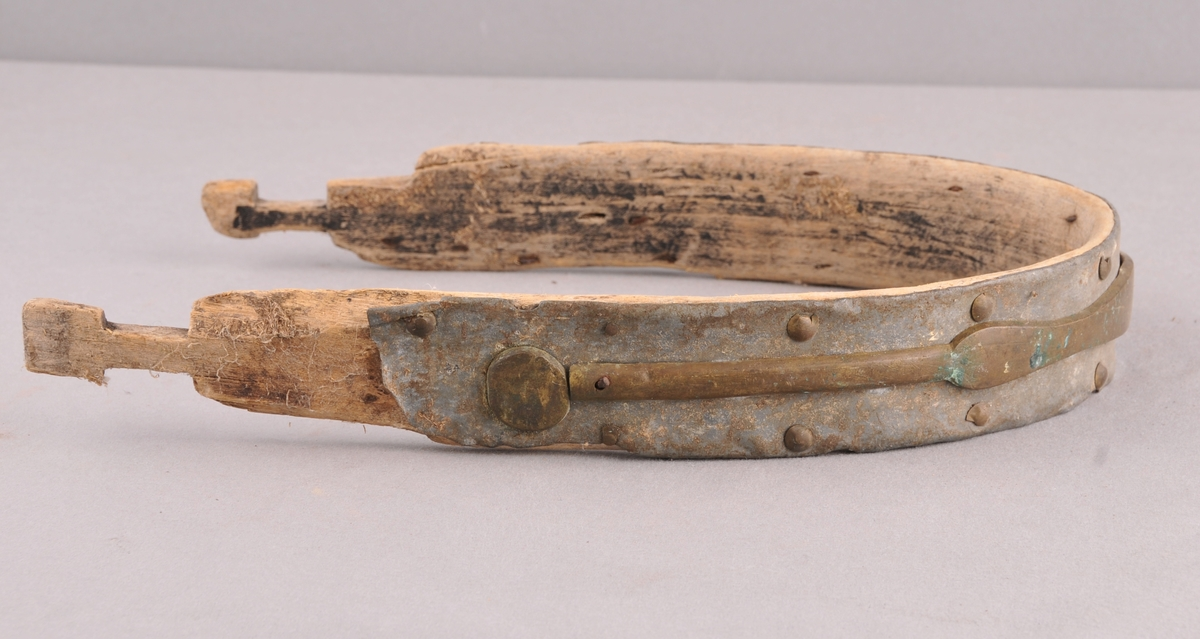 Klave av bøyd tre, beslag av blekk nagla fast på utsida, denne er dekorera med ei støypt messingrand. Skade på blekk og nessing.