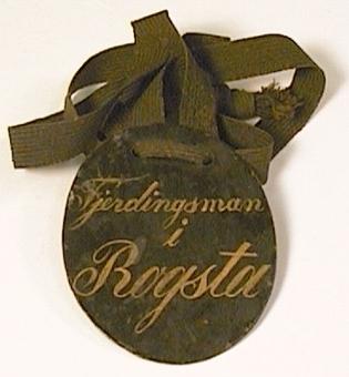 Identitetsbricka som tillhört: Fjerdingsman i Rogsta. Svartmålad plåtbricka med gul text. I brickans övre del iträtt ett mörkgrönt band.