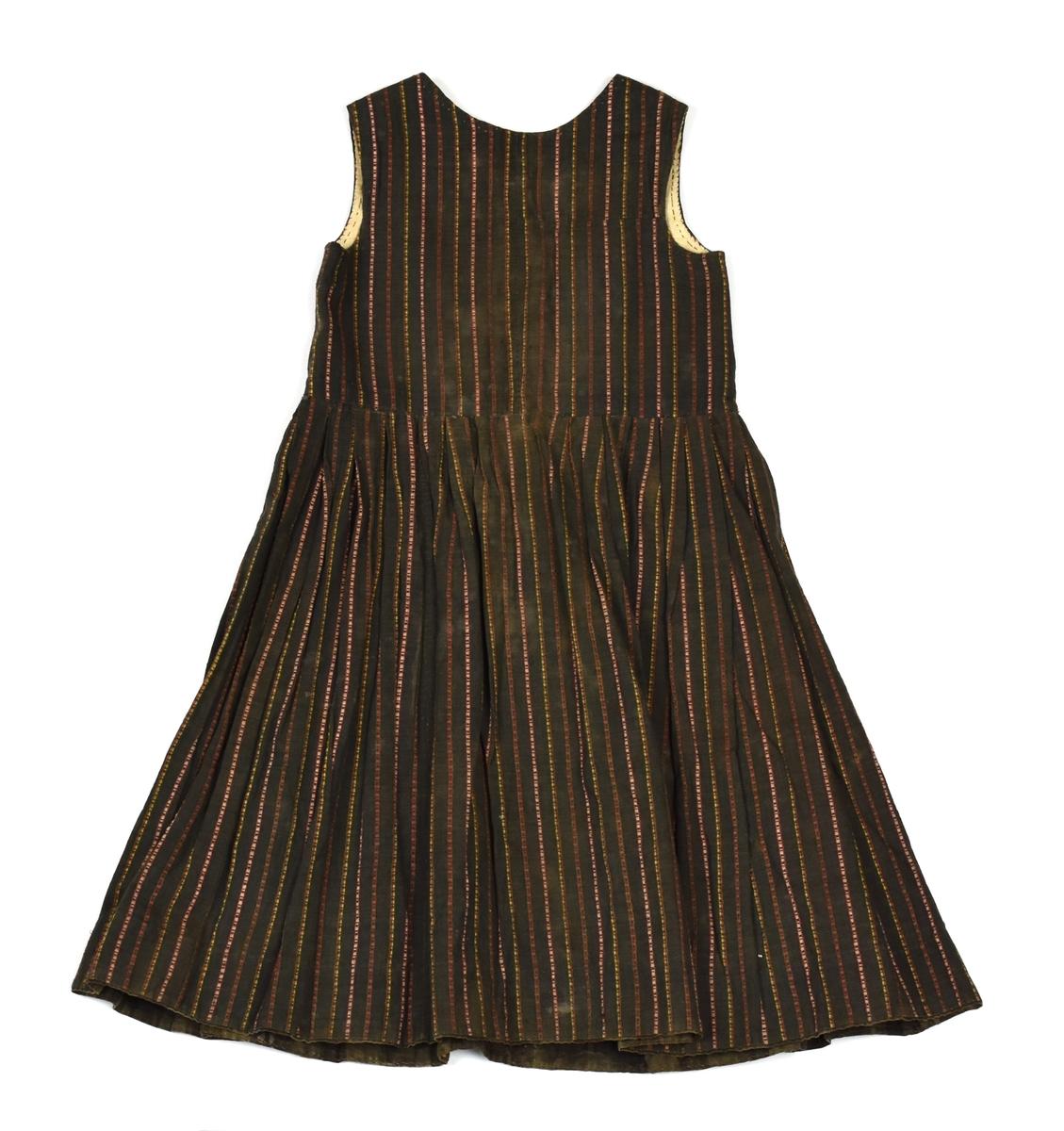 Brun kjol med smala ränder i rött, grönt, vitt och gult. Livet är fodrat med linnelärft, figursytt och knäpps med sex hyskor och hakar. Kjolen är uppfållad med grå och svartrutigt bomullstyg samt har ladga veck i midjan.