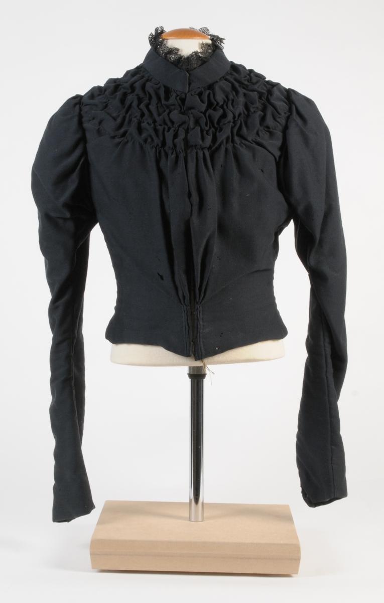 Figursytt klänningsliv av svart yllesatin med knäppning fram genom hylsor och hakar. Ärmarna är långa med puff och överdelen är rynkad på framstycket. Plagget har låg stålkrage, kantad med svart tyllspets samt är fodrat med beige bomullsväv.
