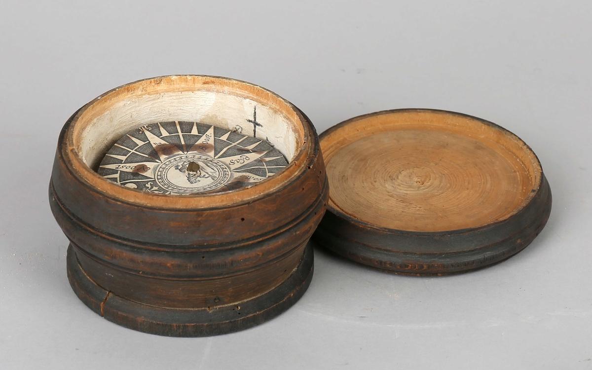 Luftkompass i dreiet trebolle med trelokk. Hoveddel bestående av bolle med metallspiss i senter til luftkompass.