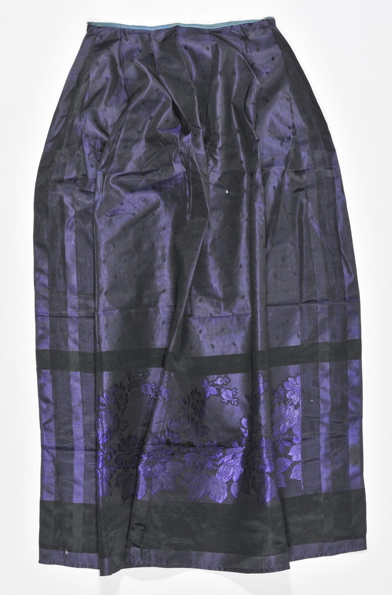 Forkle i svart og lilla silkebrokade. Motfold midt framme, og to folder på kvar side. Smal mellomblå linning øverst. Jarekantar i båe sidene, maskinfalda nederst. Linning påsydd for hand.