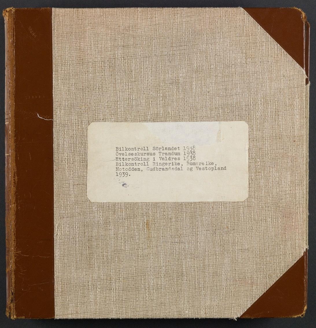Kvadratisk, beige album med ringpermsystem. Fotografiene er limt på sorte sider i papp. Maskinskrevne bildetektser på hvite papirremser. Rygg og hjørner i brunt skinn.