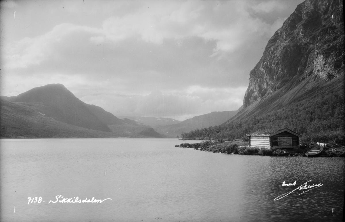 Nord-Fron. Øvre Sikkilsdalsvatn med et naust eller fiskebu og robåt i forgrunnen.