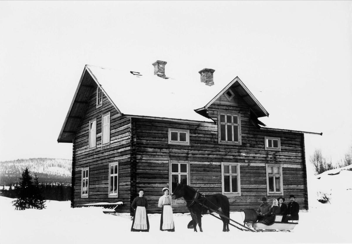 Häst och släde med fyra personer, två kvinnor står bredvid hästen, framför bostadshus