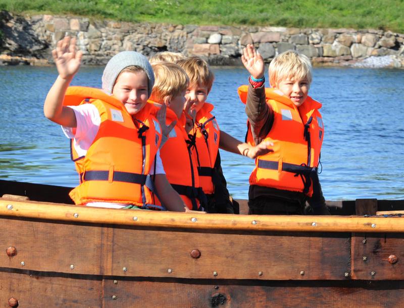 Fem barn i redningsvest ombord trebåten Vaaghals, to av barna vinker.