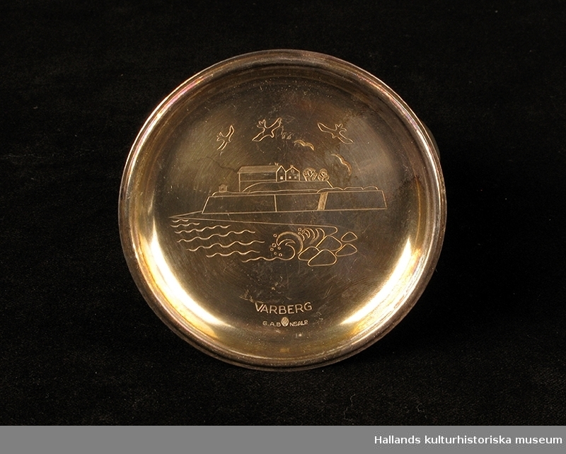 """Samling av Varbergssouvenirer. a) kakelplatta """"Varbergs fästning"""".  Mått: längd 15 cm, bredd 15 cm, höjd 1 cm. b) kakelplatta """"Varbergs fästning"""".  Mått: längd 15 cm, bredd 15 cm, höjd 1 cm. c) askfat """"Varbergs fästning"""".  Mått: längd 17 cm, bredd 9,5 cm, höjd 2,5 cm. d) glas, minne från industriutställningen 1904. Mått: diameter 5,5 cm, höjd 9,5 cm. e) glas, minne från industriutställningen 1904 Mått: diameter 5,5 cm, höjd 9,5 cm. f) äggkopp,  """"Varbergs fästning"""". Mått: diameter 4,5 cm, höjd 6 cm. g) äggkopp,  """"Varbergs stadshotell"""". Mått: diameter 4,5 cm, höjd 6 cm. h) dosa av tenn,  """"Varbergs fästning"""". Mått: diameter 7,7 cm, höjd 3 cm.  i) underlägg tenn,  """"Varbergs fästning"""". Mått: diameter 8 cm, höjd 0,5 cm. j) tennfat, """"Varbergs fästning"""". Mått: diameter 19 cm, höjd 1,5 cm. k) tennfat, """"Varbergs fästning"""" Mått: diameter 18 cm, höjd 1 cm."""