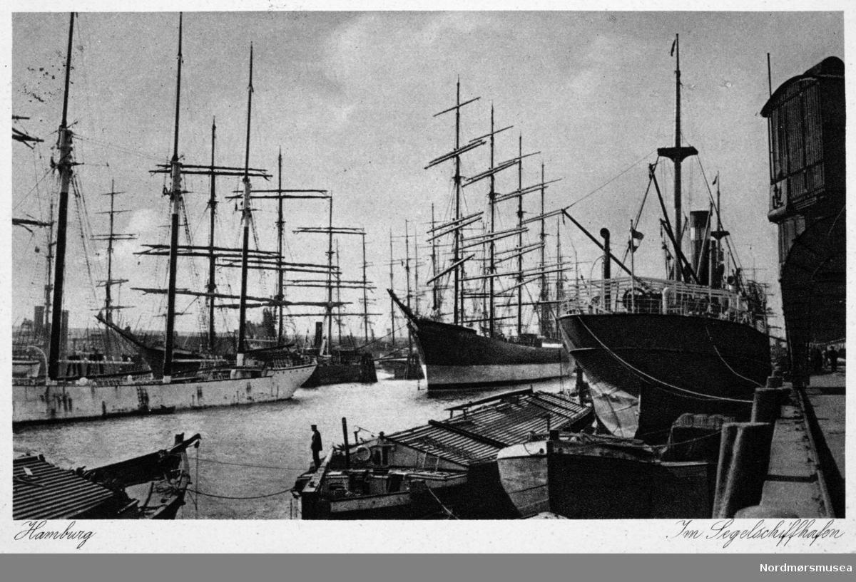 Postkort med motiv fra havna i Hamburg, her full av seilskuter samt bl.a. et dampskip fortøyd til kai. Kortet er poststemplet i Bad Bramstedt, Holstein. Fra Kaptein John Paulsens postkort og private bilder. Fra Nordmøre museums fotosamlinger.
