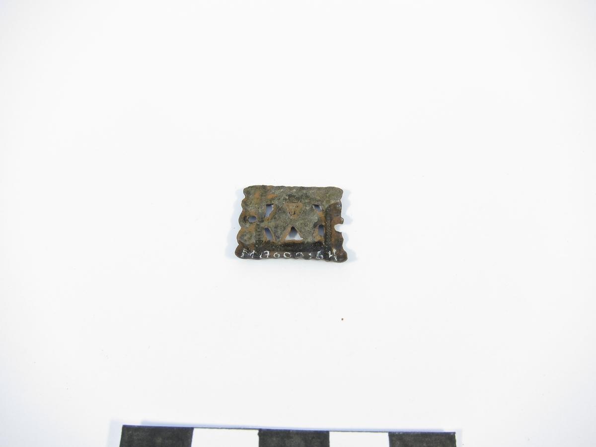 Prydnadsbeslag i form av ett rektangulärt, genombrutet pressbleck. I mitten två romber, omgivna av strierade vulster, ytterst pärlstavar. Två nithål, varav ett trasigt, men inga bevarade nitar.