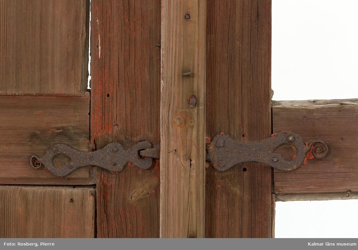 KLM 45928:1. Väggparti med fönster. Vägg bestående av liggande timmer med fastspikad stående och rödfärgad locklistpanel. Timret har på väggens insida rester av fastspikade tapeter och papp. I väggpartiet ett tvåluftsfönster med grå- och vitmålad fönsterbåge och karm. Fönsterfodret är på utsidan vitmålat och på insidan i grå kulör. Fönsterrutorna finns ej bevarade. På fönstrets utsida två stycken rödfärgade fönsterluckor med handsmidda beslag av järn. Dessa är på insidan vitmålade. Luckorna består av en ram med två speglar, varav den övre har en utsågad blomma. Ena fönsterluckan saknar båda speglarna.