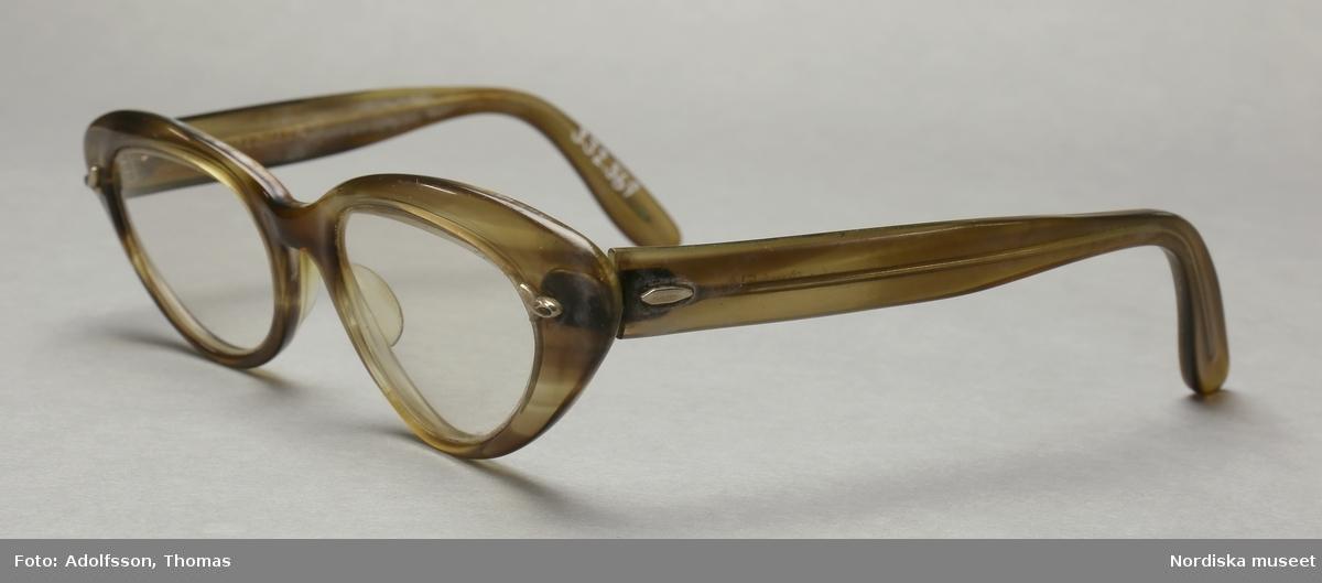 """Ett par glasögon i genomskinlig ljusbrun plast med glaslinser. Bågar i kattögon-stil med metalldetaljer på fronten samt på utsidan av skalmarna närmast gångjärnen. Sadelbrygga med slitage på insidan. På frontens baksida står det instansat """"B&L 46[]20"""".  På insidan av skalmarna står det """"Bausch & Lomb 5 1/4"""".  H +075-15 180° V +075-20 180° Zeiss """"uropal-antireflex"""" linser. Slitage på skalmarnas in- och utsidor. /Petrine Knight, 2014-12-08"""